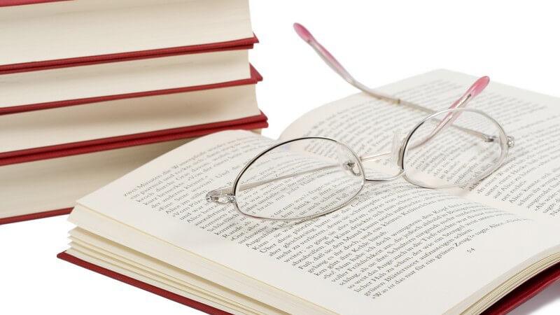 Lesebrille auf einem aufgeschlagenen Buch, dahinter ein Stapel mit weiteren roten Büchern
