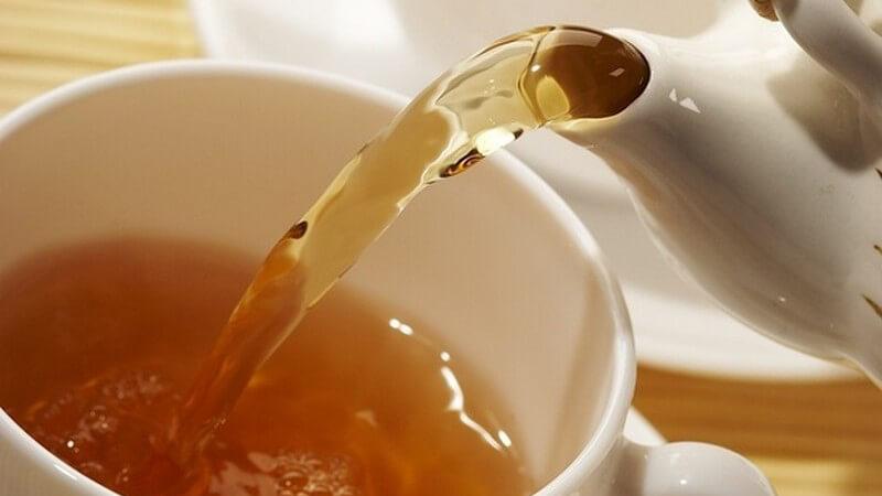 Halbvolle Teetasse vorne, weiße Teekanne schenkt schwarzen Tee o. Early Grey ein, hinten leere Teetasse, auf Holz