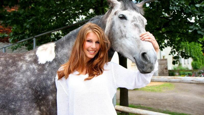 Junge Frau in weißem Oberteil mit einem grauen Pferd