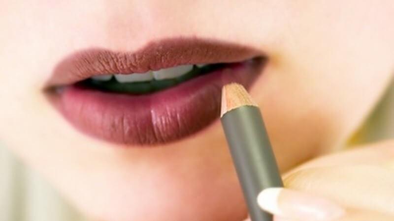 Dunkelroter Mund einer Frau wird von Lipliner bemalt