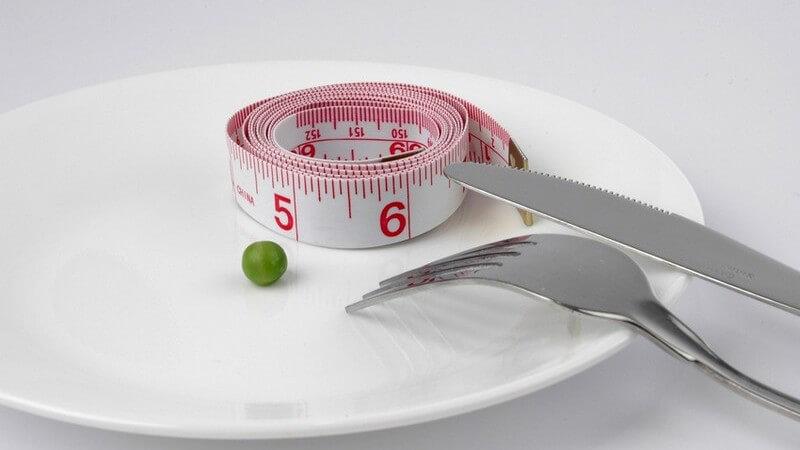 Abnehmen - Teller mit Erbse, Maßband und Besteck