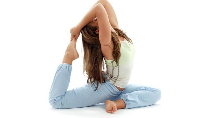 Dunkelhaarige Frau im Sportoutfit macht Yogaübung auf weißem Hintergrund