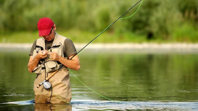 Angler mit Angel bis zu den Oberschenkeln in See