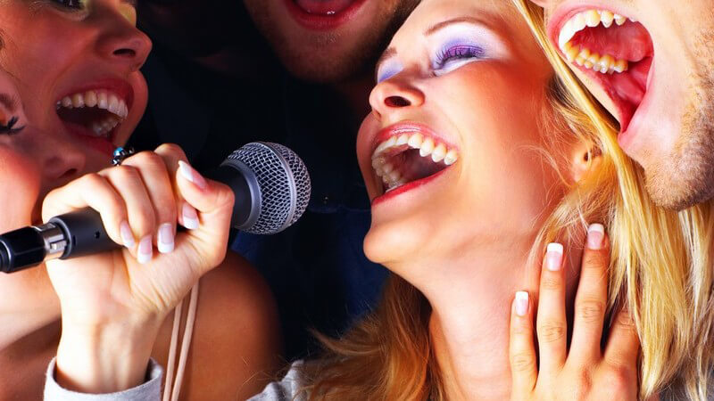 Gruppe junger Menschen singt zusammen auf Karaoke Party