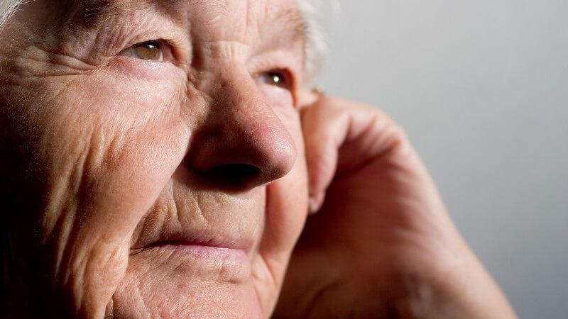 Alte Frau mit braunen Augen blickt in die Ferne, die linke Hand an der Wange