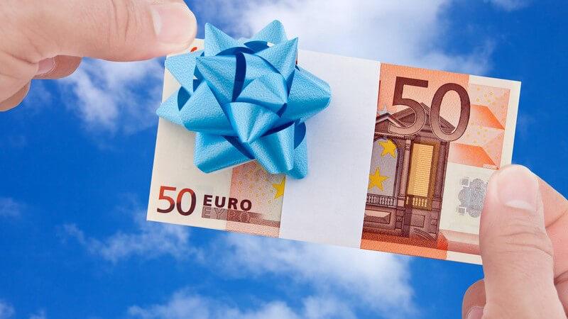 Zwei Hände halten einen 50-Euro-Geldschein mit weißem Band und blauem Schleifchen vor einen blauen Himmel