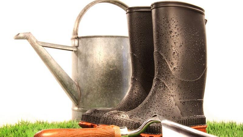 Gummistiefel, kleine Gartenschaufel und Gieskanne auf Rasen