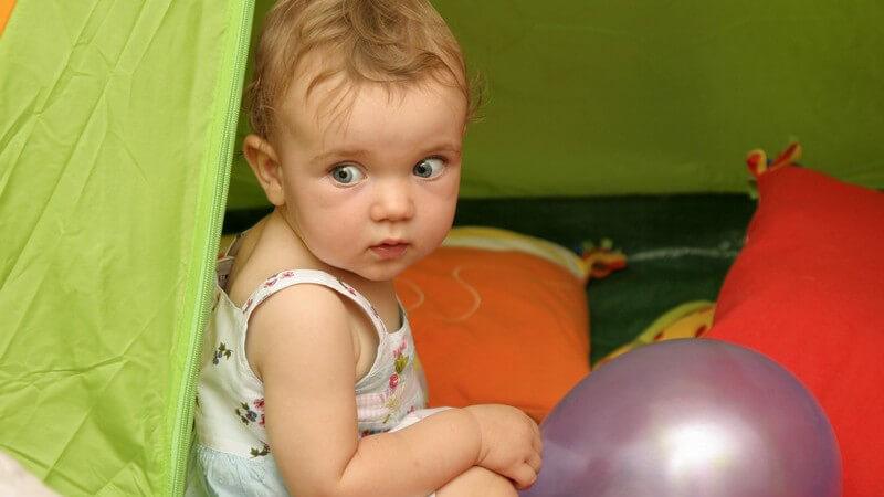 Blondes Kind in weißem Kleid sitzt in grünem Zelt mit violettem Luftballon und Kissen