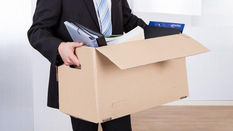 Geschäftsmann im Anzug verlässt sein Büro mit einem Umzugskarton in den Händen