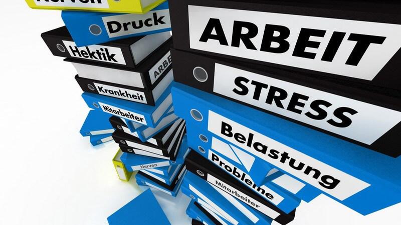 Aufeinander gestapelte Aktenordner mit Aufschrift Arbeit, Stress, Belastung etc.