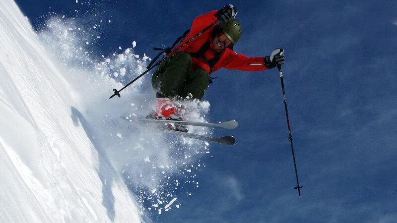 Skifahrer springt steilen Abhang hinunter