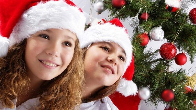 Zwei Mädchen mit Nikolausmütze vor einem geschmückten Weihnachtsbaum