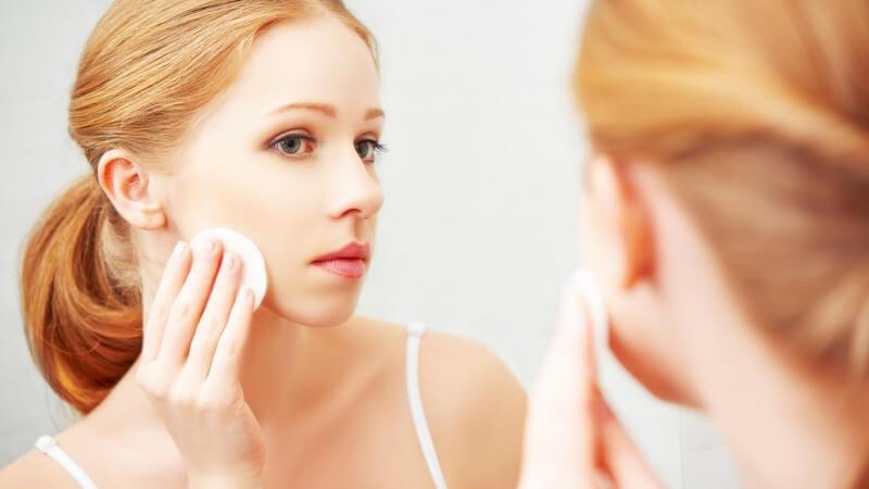 Rothaarige junge Frau steht vor dem Spiegel und entfernt Make-up mit einem Wattepad