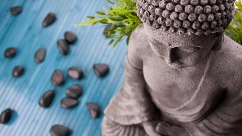 Buddha-Statue neben schwarzen Basaltsteinen auf blaumem Grund