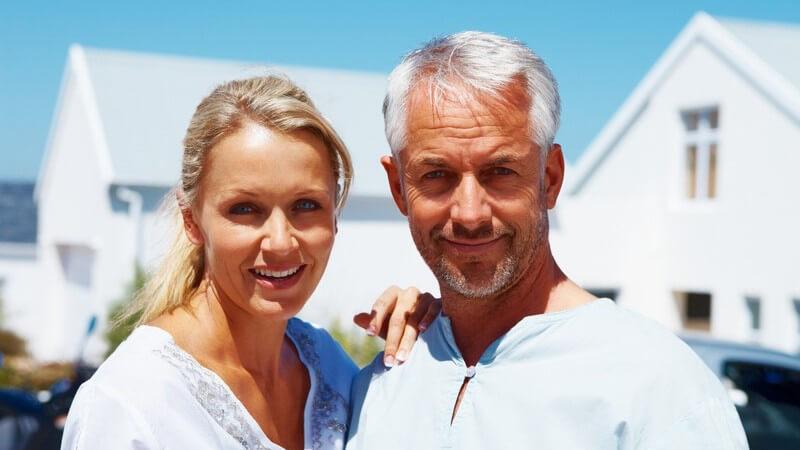 Älteres Paar lächelt in Kamera, im Hintergrund Meer