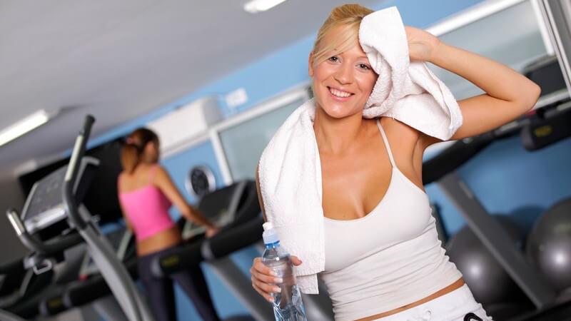Frau mit Wasserflasche und Handtuch im Fitnesstudio
