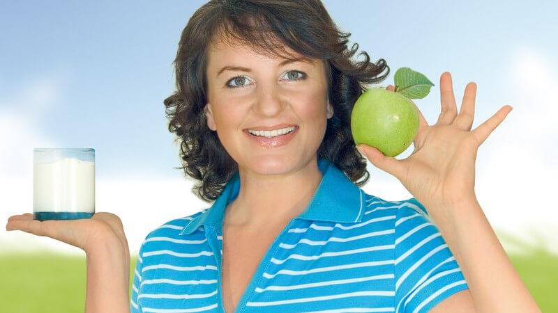 Dunkelhaarige, lächelnde Frau hält grünen Apfel und ein Glas Milch