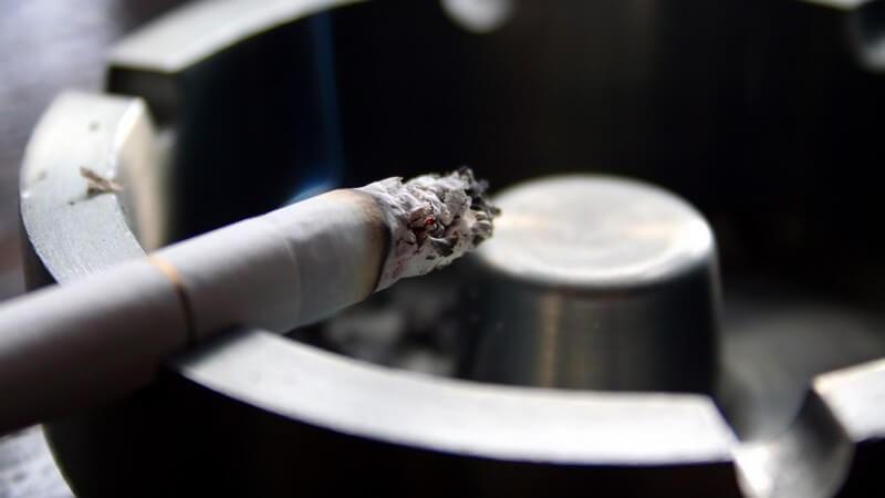 Brennende Zigarette im Aschenbecher